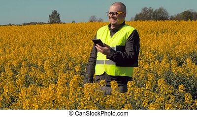 Happy farmer with tablet PC on rape field laughing