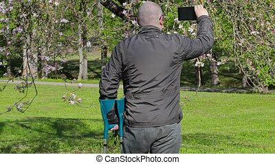 Disabled man with crutches filmed as blossoming apple tree