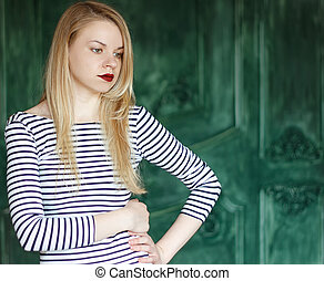 Blonde with red lips in a striped shirt on a green...