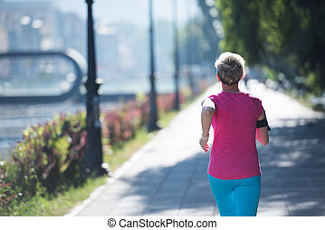 sporty woman running  on sidewalk