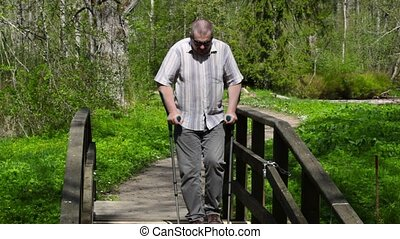 Disabled man with crutches walking on bridge