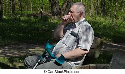 Tired disabled man with crutches on bench in the park