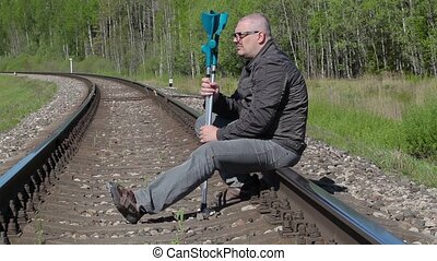 Depressed disabled man with crutches sitting on railway