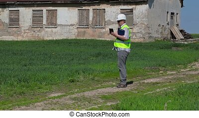 Building inspector filming on tablet PC near old abandoned,...