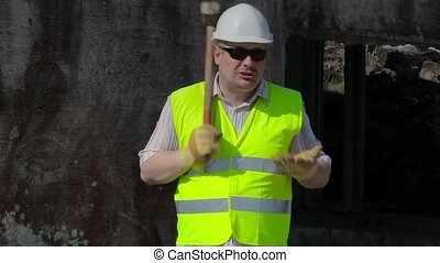Angry Construction worker with sledgehammer talking near...