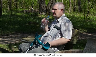 Disabled man with crutches sitting on the bench and drinking...