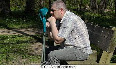 Depressed disabled man with crutches on bench in the park