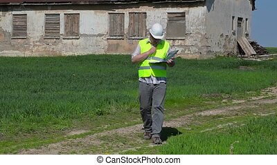 Building inspector writing near old abandoned, damaged house...