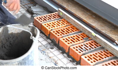Builder lays bricks on a construction site - Brickwork...