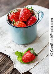 Fresh juicy strawberries in old rusty mug. Rustic wooden...