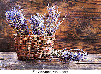 bunches of dried lavender in backet on wooden background