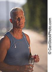 senior jogging man drinking fresh water from bottle -...
