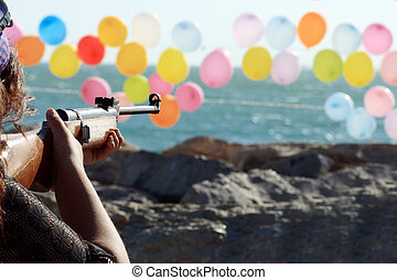 Shooting Range - Women shooting a gun for colored balloons...