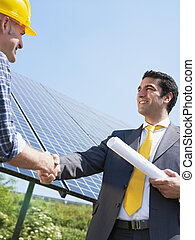 businessman and electrician shaking hands - Portrait of mid...