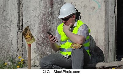 Construction worker thinking and using tablet PC near wall