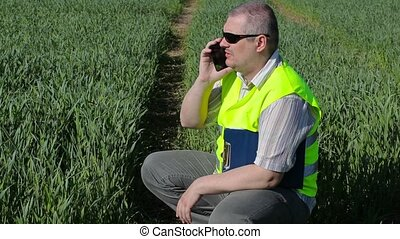 Farmer with smartphone and folder at the green cereal field