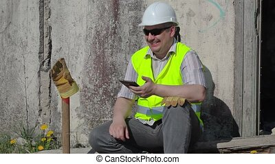 Happy construction worker with tablet laughing PC near wall