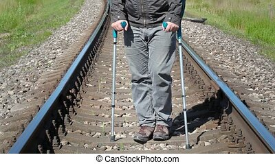 Disabled man with crutches on railway