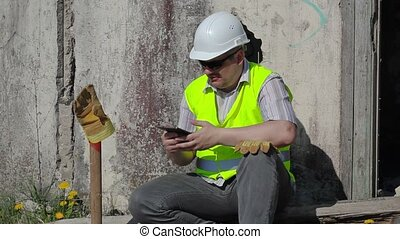 Angry construction worker with tablet PC near wall