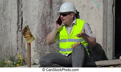 Angry construction worker talking on smart phone near wall