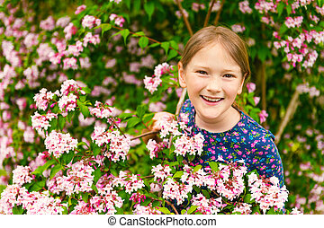 Outdoor portrait of a cute little girl of 8-9 years old,...