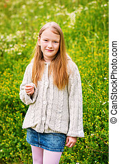 Outdoor portrait of adorable little girl of 8-9 years old,...