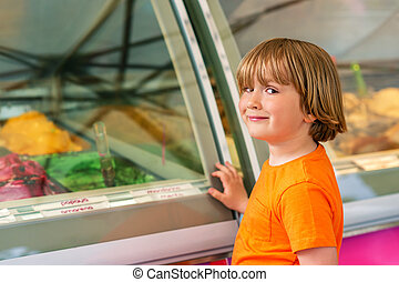 Sweet little boy choosing dessert in ice cream shop