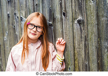 Outdoor portrait of a cute little girl in glasses, standing against old wooden background