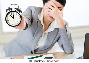 Young asian businesswoman worried about time in office
