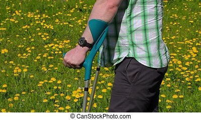Disabled man with crutches on the dandelion field