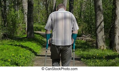 Disabled man with crutches on path in the park