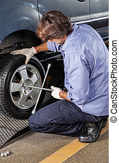 Mechanic Fixing Car Tire With Rim Wrench At Garage - Side...