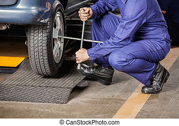 Mechanic Crouching While Fixing Car Tire - Low section of...