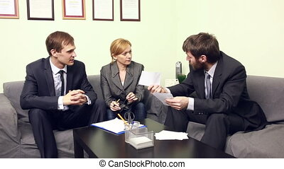 three co-workers discussing business plan in office.