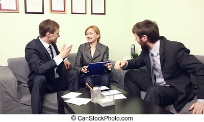 three co-workers discussing business plan in office -...