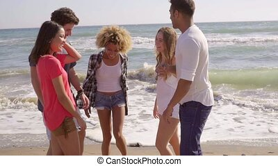 Young People Standing On The Beach.