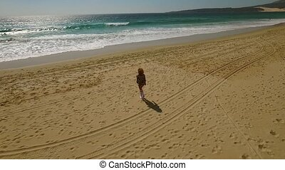 Young woman walking alone along a beach - Young woman...