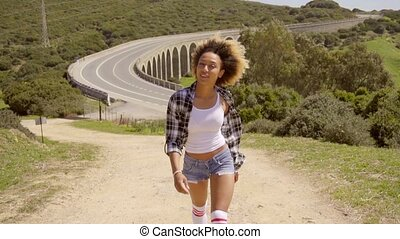 Black Woman Walks Along An Empty Road - Portrait of young...