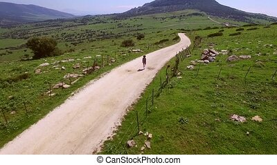 Aerial View Of Hilly Terrain With Walking Woman - The camera...