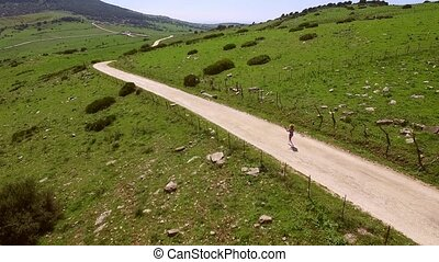 Hilly Terrain With Walking Woman - The camera flies over the...