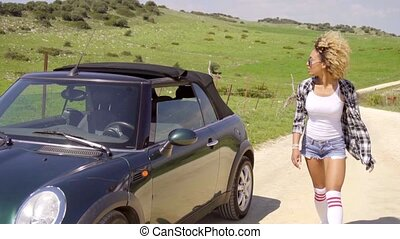 Woman looking around car. - Young sexy afro-american woman...