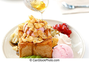 Honey toast and whipping cream with strawberry ice cream on...