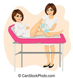 Young beautician waxing young woman legs lying on spa bed -...