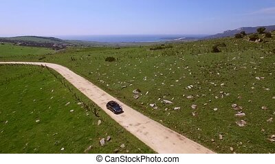 Single car driving on country road - View from the sky of...