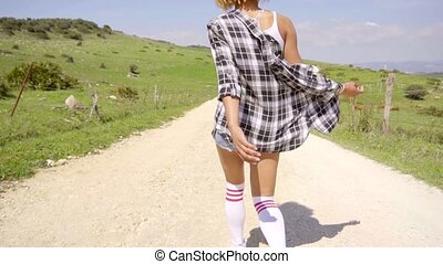 Rear view of woman in shorts walking down hill on gravel...