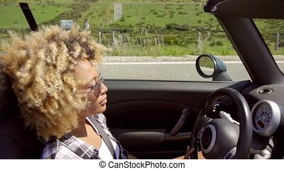 Young woman with a trendy afro hairstyle driving her sports...