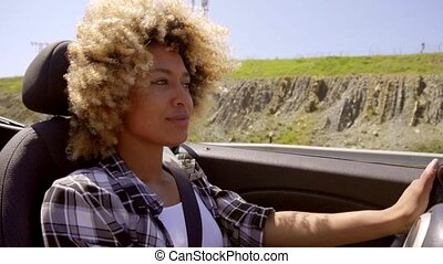 Pretty young woman driving her cabriolet car along a rural...