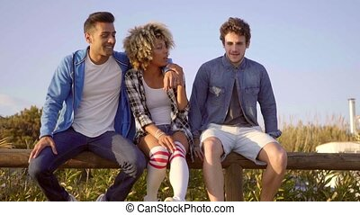 Young People Sitting On Wooden Fence. - Young mixed-race...