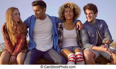 Young People On Wooden Fence - Five young mixed-race people...