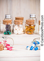 Blue and pink capsules in glass containers